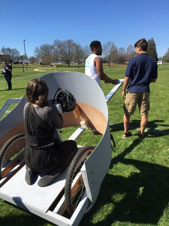 Senior Kameron Shook bracing herself for the chariot race, while fellow seniors Timothy Spivey and Kobe van Someren prepare to pull the chariot.