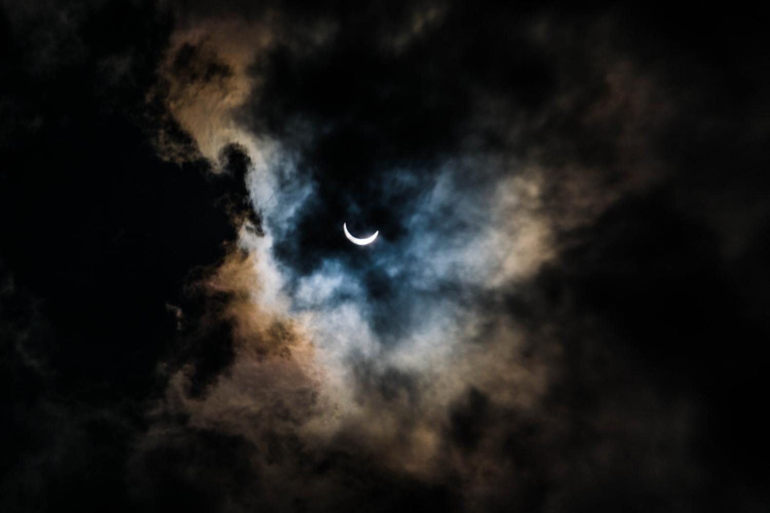 The+solar+eclipse+as+seen+by+onlookers+during+its+peak+coverage.+