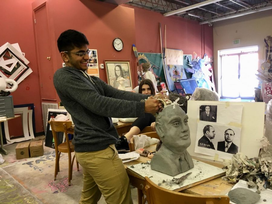 Student+Smith+Patel+sculpts+a+bust+out+of+clay+in+sculpture+class.