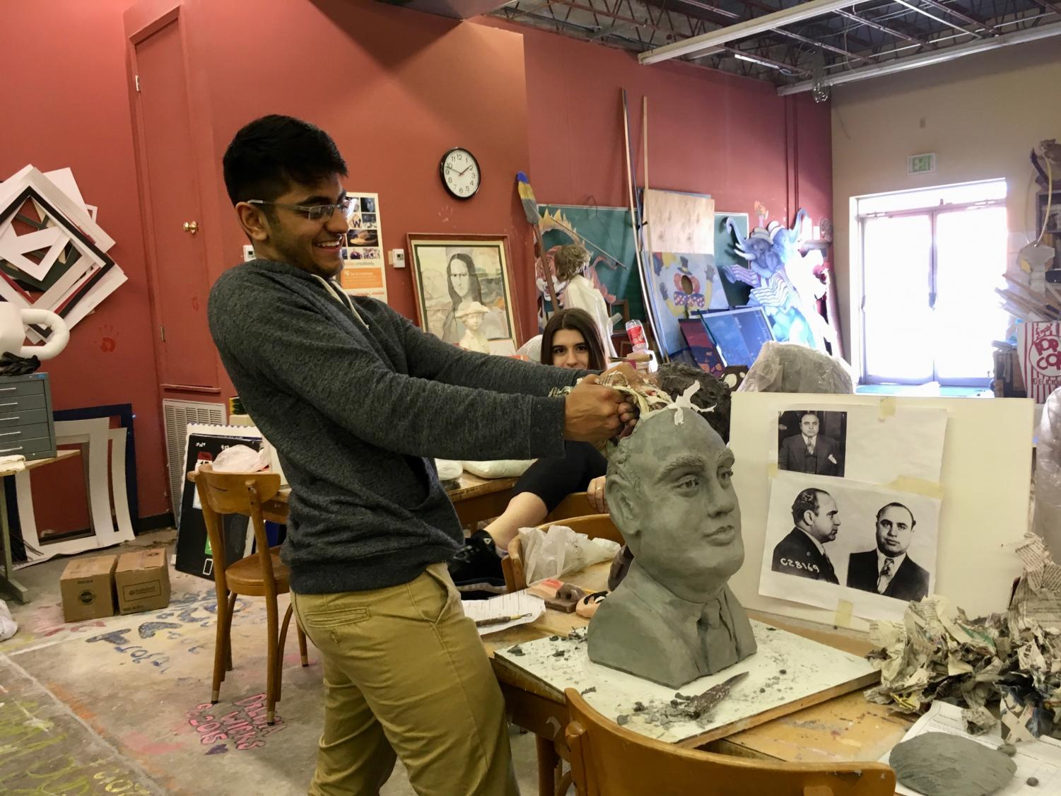 Student Smith Patel sculpts a bust out of clay in sculpture class.