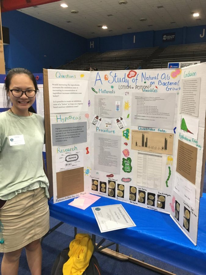 Liz+posing+with+her+science+fair+project+that+she+conducted+by+seeing+the+effects+of+essential+oils+on+E.+coli.+