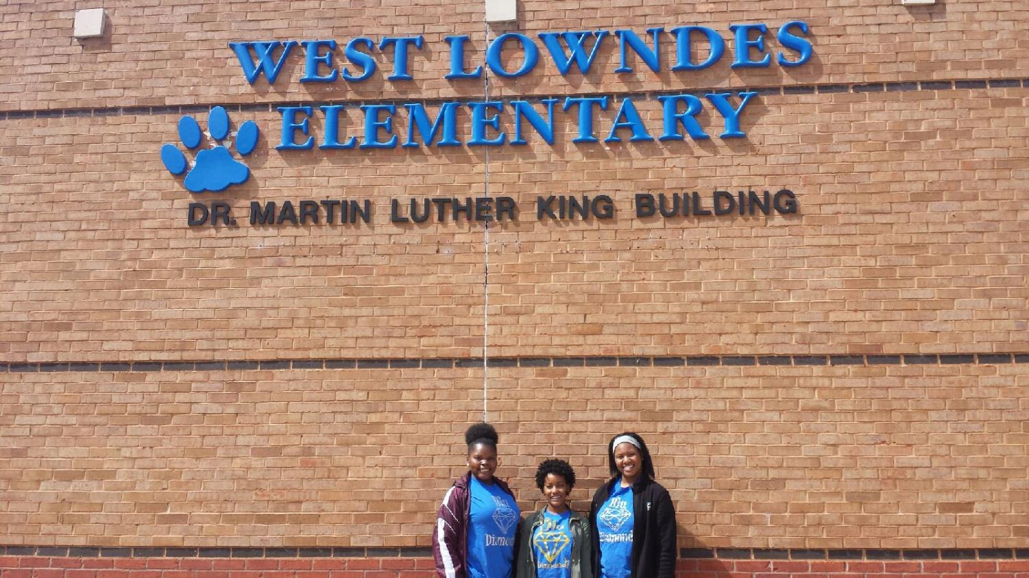 Three Blu Diamondz members, Tija Johnson, Ashley McPherson, and Ta'Kiya Moore, prepare for the Easter Egg Hunt and book reading at West Lowndes Elementary School.