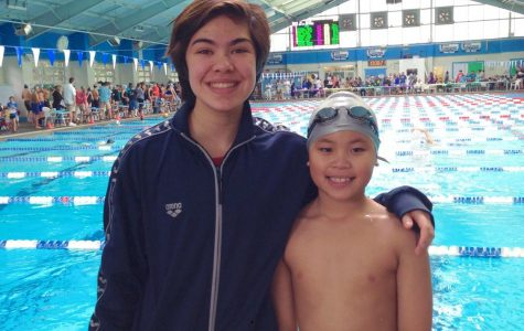Sara stands with her younger cousin at the Biloxi Natitorium during a swim meet.