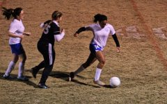 Erin Williams runs with the ball while Ashley Nguyen tries to hold back an opponent.