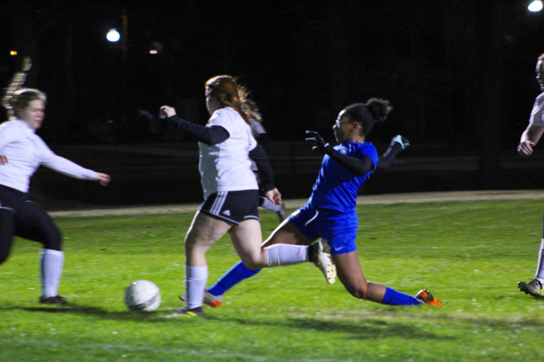 Senior Erin Williams hurdles toward the ball.