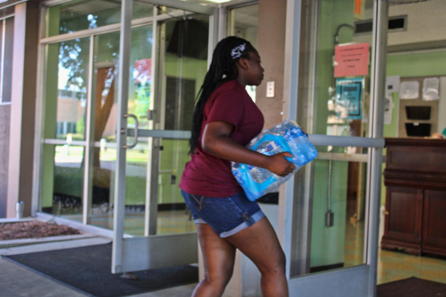 Senior Violet Jira carries in a pack of water during move in day.