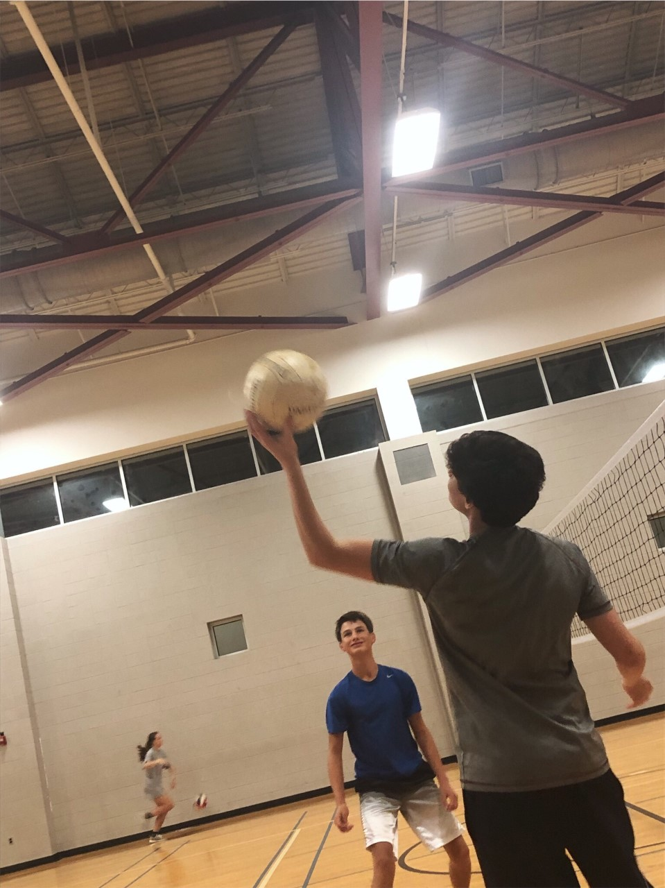 Two players practice passing the volleyball.