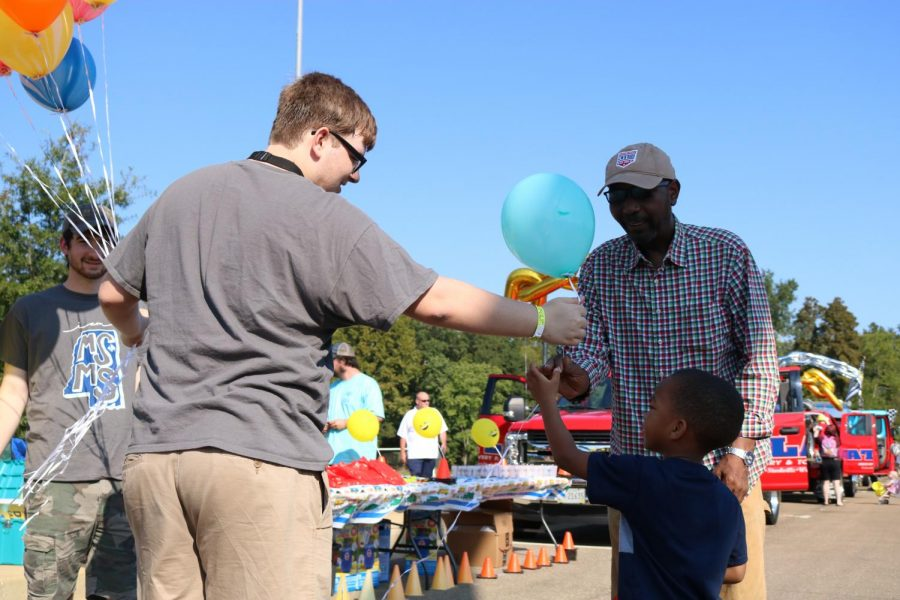 Junior David Gipson hands out balloons for the children.