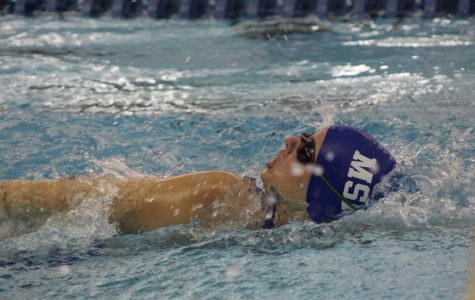 Captain Samantha Broussard swims in the 100 yard backstroke event.