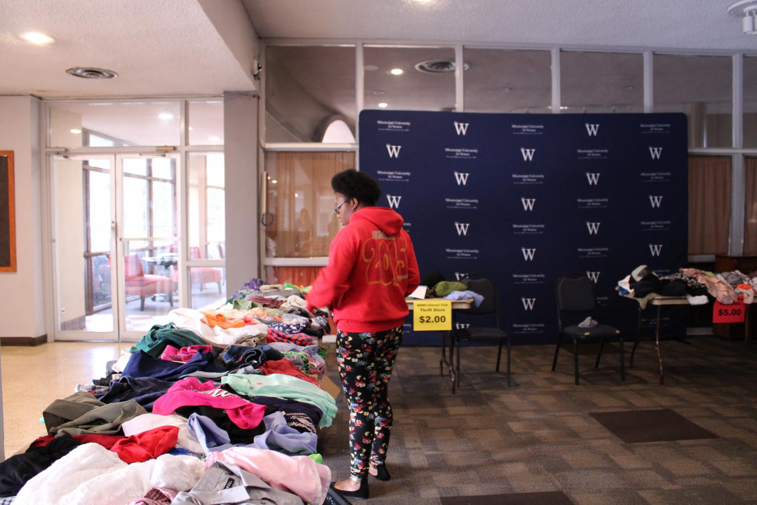 A student looks at one of the tables of donated clothes, hoping to get a steal.