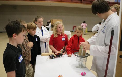 Several elementary students look on as MSMS students demonstrate inertia.