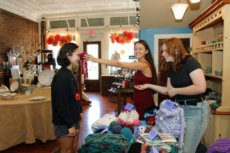 Students Cecile Roberts and Linda Arnoldus visit Alden Wiygul's stand at Park Place Boutique.