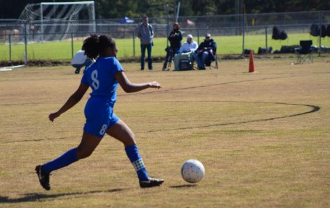 Captain Tierah Macon runs to kick the ball.