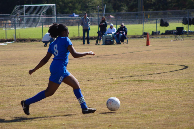 Captain Tierah Macon runs to kick the ball.