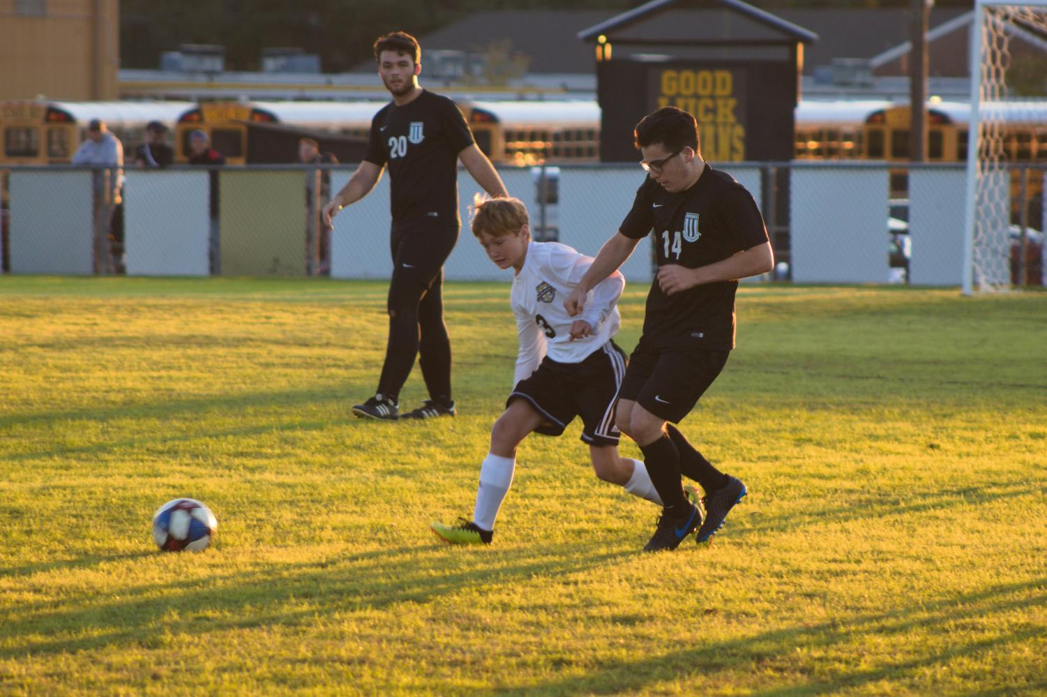 Junior Max Grossman races another player to the soccer ball.