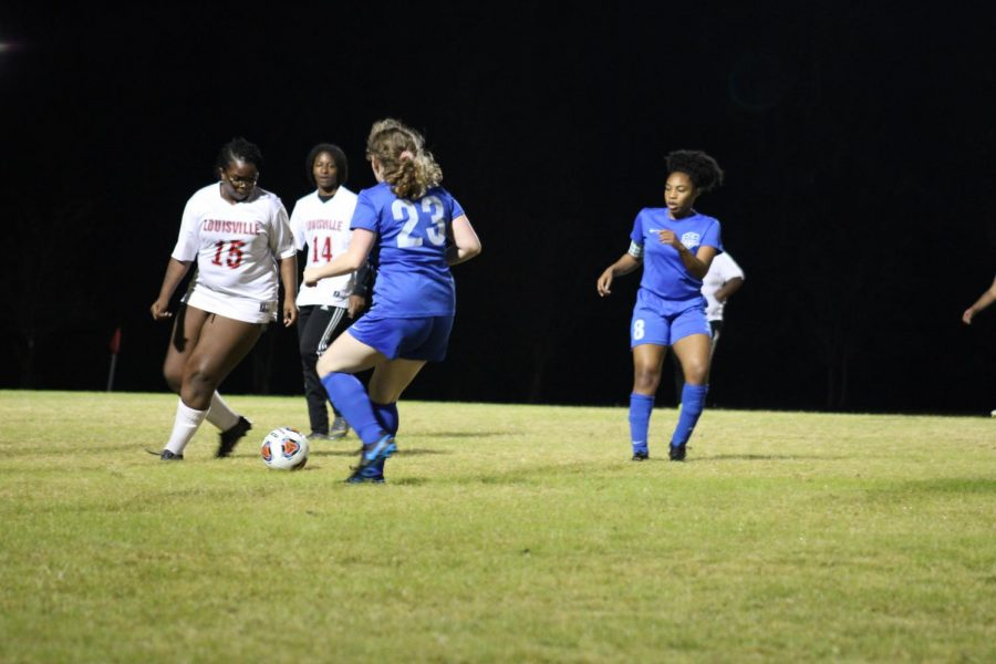 Seniors Whitley Hester and Tierah Macon battle with the Cardinals defense over possession of the ball.