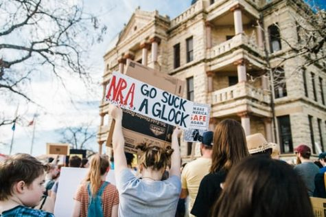 """A marcher holds up a sign reading, """"NRA go suck a glock."""""""
