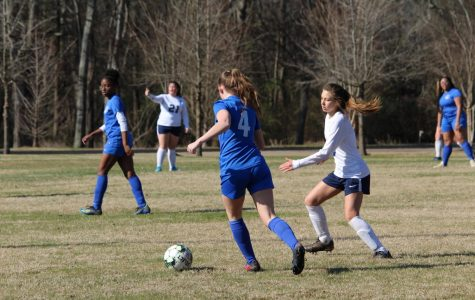 Senior Samantha Broussard chases down the ball as an opponent approaches her.