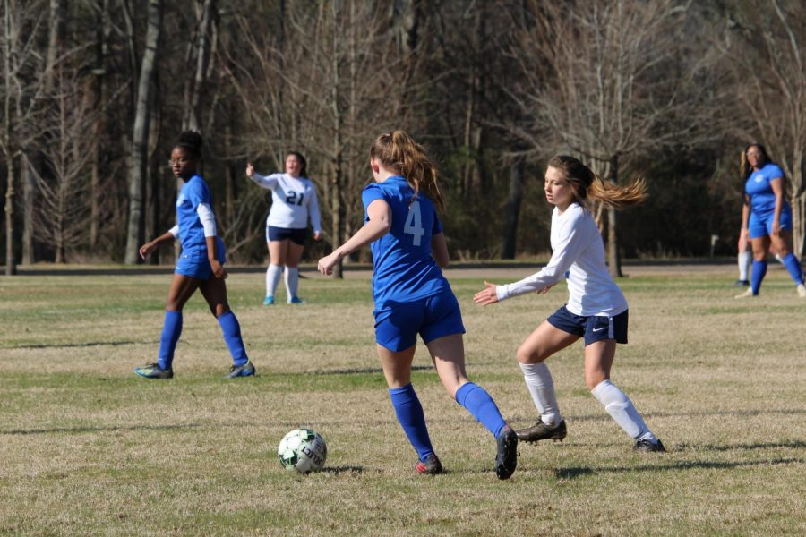 Senior+Samantha+Broussard+chases+down+the+ball+as+an+opponent+approaches+her.