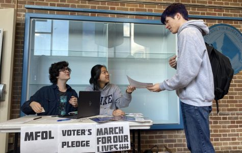 From left to right, junior Zach Medlin and Nina Vo run the March for Our Lives voter's pledge table.