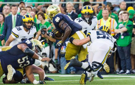 The Michigan Wolverines (white jerseys) play in the Big 10, which has already canceled its season. Notre Dame (blue jerseys) play as independents, leading to numerous challenged with game cancelations.