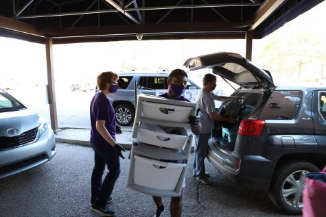 Emissaries help families unload and move items into the dorms.