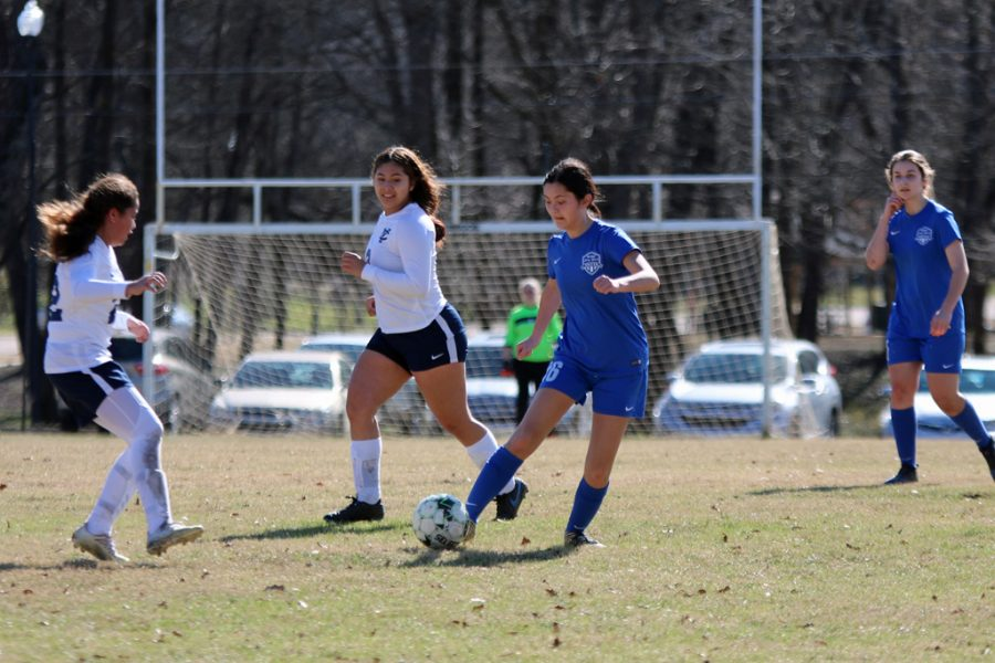 Senior Weslyn McMurrin swerves between players before taking a shot.