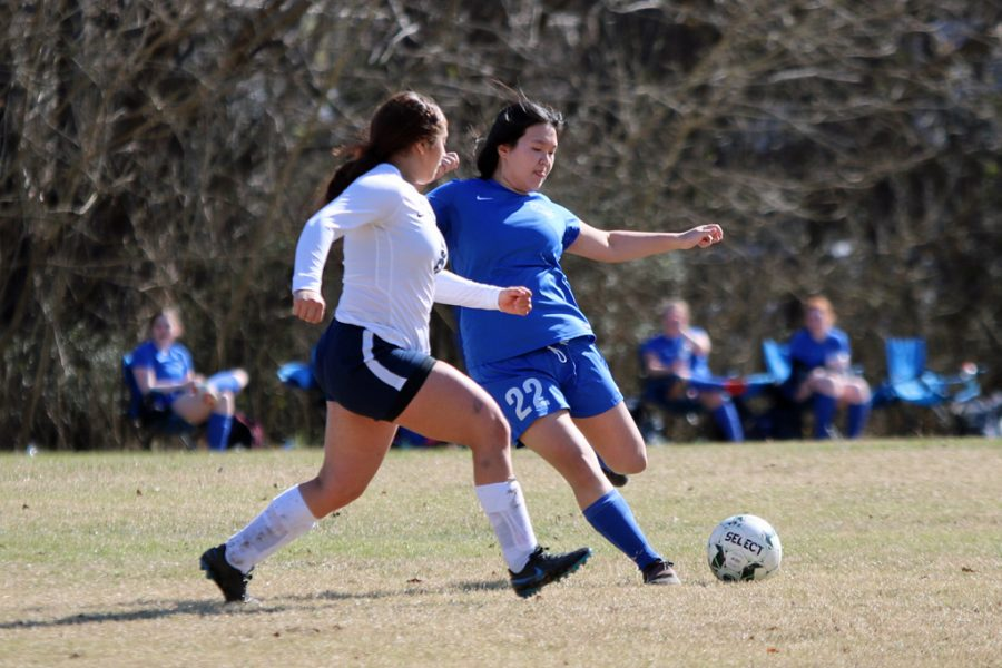 Senior Karlene Deng aims to hit the ball before the player from Yazoo County.