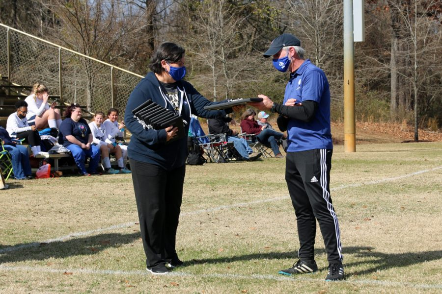 Kelly Brown, Director for Academic Affairs, (left) recognizes Coach Yarborough (right)  for his time coaching the girls' team.