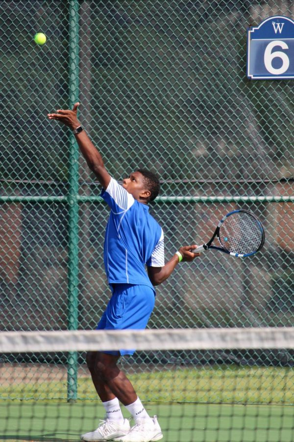 Senior Sam Hill keeps his eyes trained on the ball as he serves.